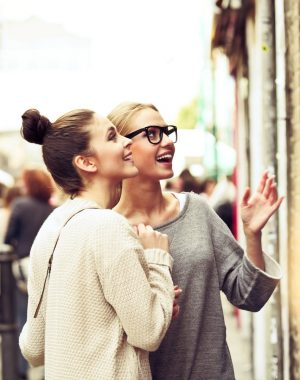 Female friends standing at a shopwindow, having fun.